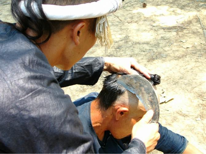 Haircut with a reaphook of Basha minority nationality in Guizhou province.
